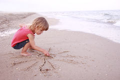La muchacha dibuja un sol en la arena en la playa Foto de archivo libre de regalías