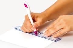 La muchacha dibuja una pluma en una regla en el papel Foto de archivo