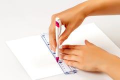 La muchacha dibuja una pluma en una regla en el papel Foto de archivo libre de regalías