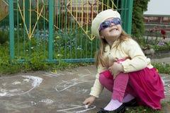 La muchacha dibuja una tiza Fotos de archivo libres de regalías