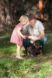 La muchacha dice algo al padre, mirando dos perros Foto de archivo libre de regalías