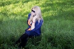 La muchacha dice por el teléfono en un césped, una hierba verde Fotos de archivo libres de regalías