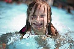 La muchacha disfruta de día de verano en la piscina. Fotografía de archivo libre de regalías