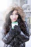 La muchacha disfruta de la bebida caliente mientras que lleva la chaqueta del invierno Fotografía de archivo libre de regalías