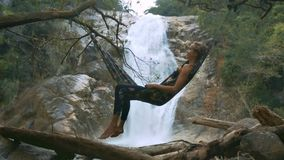 La muchacha disfruta de las vacaciones que mienten en la hamaca contra la cascada