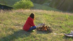 La muchacha disfruta de la reconstrucción al aire libre Freír las salchichas en el fuego Comida campestre por la tarde en natural metrajes