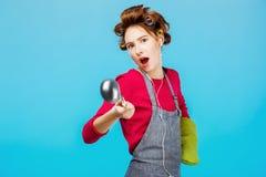 La muchacha divertida baila mientras que cocina la cena con el guante verde a mano Fotografía de archivo libre de regalías