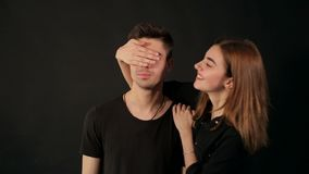 La muchacha divertida cierra los ojos de las manos del ` s del individuo en fondo negro almacen de metraje de vídeo