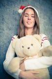 La muchacha divertida con el oso de peluche muestra la lengua Fotos de archivo libres de regalías