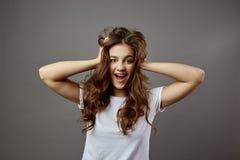 La muchacha divertida con el pelo marrón largo vestido en una camiseta blanca lleva a cabo sus manos en su cabeza en el estudio e fotos de archivo libres de regalías