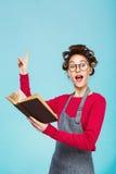 La muchacha divertida con los bigudíes y los vidrios lee y señala Fotos de archivo libres de regalías