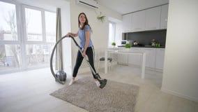La muchacha divertida del ama de casa que hace vacíos de limpieza y tiene baile de la diversión y canta en sitio en casa almacen de video