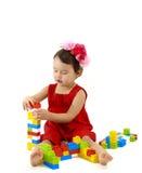 La muchacha divertida del niño que jugaba con la construcción fijó sobre blanco Imagen de archivo libre de regalías