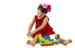 La muchacha divertida del niño que jugaba con la construcción fijó sobre blanco Foto de archivo libre de regalías