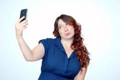 La muchacha divertida hace muecas y hace el selfie en smartphone Foto de archivo libre de regalías