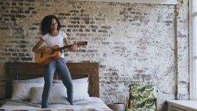 La muchacha divertida joven de la raza mixta que toca la guitarra acústica y tiene baile de la diversión en cama en casa Foto de archivo