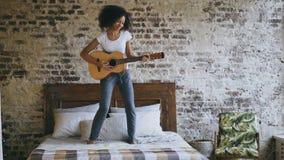 La muchacha divertida joven de la raza mixta que toca la guitarra acústica y tiene baile de la diversión en cama en casa Imágenes de archivo libres de regalías
