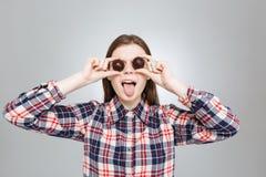 La muchacha divertida la cubrió los ojos con los caramelos y lengua el mostrar Imagen de archivo libre de regalías