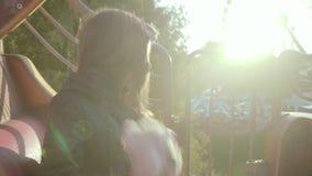 La muchacha divertida monta en un cruce giratorio, considera y da vuelta alrededor con su oso de peluche la puesta del sol en el  almacen de video