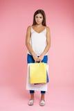 La muchacha divertida parece triste sosteniendo el manojo de bolsos después de hacer compras Foto de archivo libre de regalías