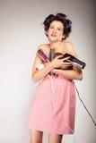 La muchacha divertida que diseña el pelo sostiene muchos accesorios Imagenes de archivo