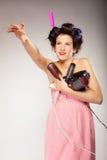 La muchacha divertida que diseña el pelo sostiene muchos accesorios Imagen de archivo libre de regalías