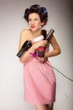 La muchacha divertida que diseña el pelo sostiene muchos accesorios Fotografía de archivo libre de regalías