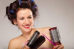 La muchacha divertida que diseña el pelo sostiene muchos accesorios Imágenes de archivo libres de regalías