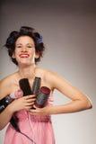 La muchacha divertida que diseña el pelo sostiene muchos accesorios Imagen de archivo