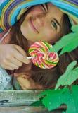 La muchacha divertida que lleva un sombrero colorido con la piruleta en ventana con la uva se va Imagen de archivo