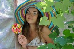 La muchacha divertida que lleva un sombrero colorido con la piruleta en ventana con la uva se va Imagen de archivo libre de regalías
