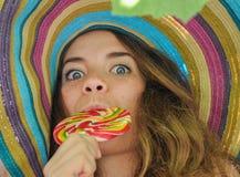 La muchacha divertida que lleva un sombrero colorido con la piruleta en ventana con la uva se va Foto de archivo libre de regalías