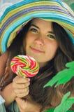 La muchacha divertida que lleva un sombrero colorido con la piruleta en ventana con la uva se va Fotos de archivo