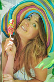 La muchacha divertida que lleva un sombrero colorido con la piruleta en ventana con la uva se va Fotos de archivo libres de regalías