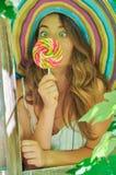 La muchacha divertida que lleva un sombrero colorido con la piruleta en ventana con la uva se va Imágenes de archivo libres de regalías