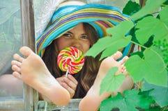 La muchacha divertida que lleva un sombrero colorido con la piruleta y que muestra sus pies en ventana con la uva se va Foto de archivo libre de regalías
