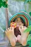 La muchacha divertida que lleva un sombrero colorido con la piruleta y que muestra sus pies en ventana con la uva se va Fotos de archivo libres de regalías