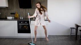 La muchacha divertida se está divirtiendo, al hacer la limpieza de la casa, baile extravagante alrededor de la escoba en cocina metrajes