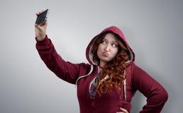 La muchacha divertida se fotografía en smartphone Foto de archivo