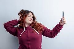 La muchacha divertida se fotografía en smartphone Imagen de archivo libre de regalías