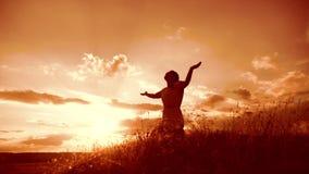 la muchacha dobló sus manos en forma de vida de la silueta del rezo en la puesta del sol mujer que ruega en sus rodillas vídeo de metrajes