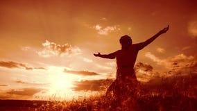 la muchacha dobló sus manos en silueta del rezo en la puesta del sol mujer que ruega en sus rodillas vídeo de la cámara lenta La  almacen de video