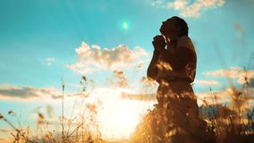 la muchacha dobló sus manos en silueta del rezo en la puesta del sol mujer que ruega en sus rodillas vídeo de la cámara lenta La  metrajes