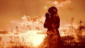 la muchacha dobló sus manos en silueta del rezo en la puesta del sol mujer que ruega en sus rodillas vídeo de la cámara lenta La  almacen de metraje de vídeo
