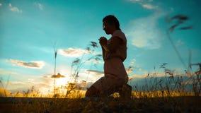 la muchacha dobló sus manos en silueta del rezo en la puesta del sol vídeo de la cámara lenta La muchacha dobló sus manos en rezo almacen de video