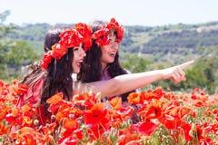 La muchacha dos está mirando alrededor en campo de la amapola Fotografía de archivo