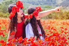 La muchacha dos está mirando alrededor en campo de la amapola Foto de archivo
