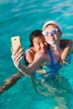 La muchacha dos se fotografió en el teléfono Foto de archivo
