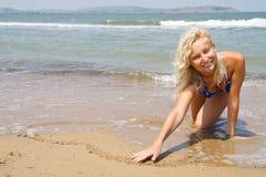 La muchacha drena un corazón en la arena Fotos de archivo libres de regalías