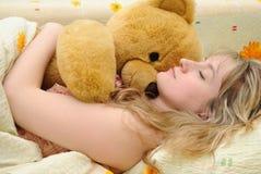 La muchacha duerme con un oso del juguete Fotografía de archivo libre de regalías